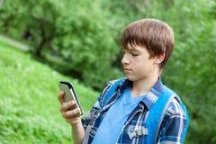 Szczęśliwy nastolatek jest usytuowanym na trawie w parku Fotografia Royalty Free