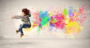 Szczęśliwy nastolatka doskakiwanie z kolorowym atramentu splatter na miastowym backg Zdjęcia Royalty Free
