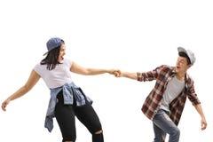 Szczęśliwy nastoletni chłopak ciągnie nastoletniej dziewczyny zdjęcia royalty free