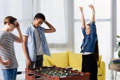 szczęśliwy nastoletni dzieciaka wygrania stołu futbol przy wielokulturowymi nastolatkami obrazy royalty free