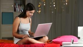 Szczęśliwy nastoletni gmeranie w laptopie w nocy na łóżku zbiory wideo