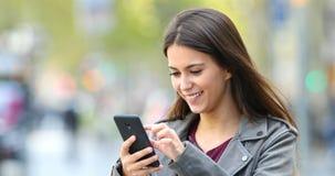 Szczęśliwy nastoletni wyszukiwać na telefonie w ulicie zdjęcie wideo