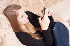 Szczęśliwy nastoletni z telefonu komórkowego obsiadaniem na kanapie w żywym pokoju Zdjęcia Royalty Free