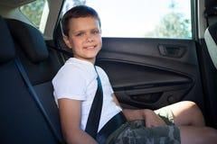 Szczęśliwy nastoletniego chłopaka obsiadanie w tylnym siedzeniu samochód Zdjęcie Stock