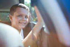 Szczęśliwy nastoletniego chłopaka obsiadanie w tylnym siedzeniu samochód Obraz Royalty Free