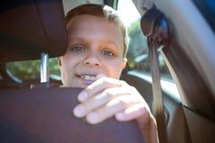 Szczęśliwy nastoletniego chłopaka obsiadanie w tylnym siedzeniu samochód Fotografia Stock