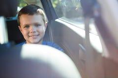 Szczęśliwy nastoletniego chłopaka obsiadanie w tylnym siedzeniu samochód Zdjęcie Royalty Free