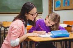 Szczęśliwy nauczyciel pomaga jej uczni obrazy stock
