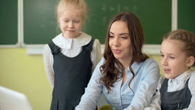 Szczęśliwy nauczyciel używa laptop z uczniami w sala lekcyjnej zbiory