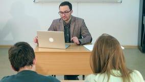 Szczęśliwy nauczyciel z laptopem daje lekci klasa zbiory