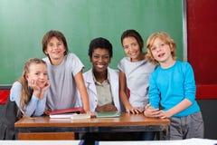 Szczęśliwy nauczyciel Z uczniami Przy biurkiem Zdjęcia Royalty Free