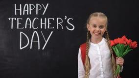 Szczęśliwy nauczyciela dzień pisać na blackboard, uczennica trzyma wiązkę tulipany zdjęcie wideo