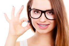 Szczęśliwy nerdy nastoletni z brasem jest ubranym eyeglasses zdjęcia stock