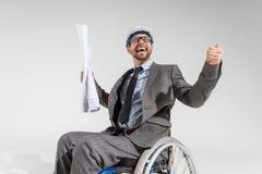 Szczęśliwy niepełnosprawny architekt w wózku inwalidzkim z projektami obrazy stock