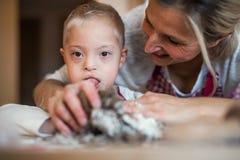 Szczęśliwy niepełnosprawny puszka syndromu dziecko z jego matką indoors piec zdjęcie stock