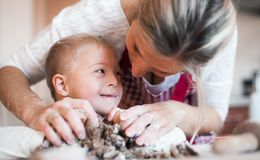 Szczęśliwy niepełnosprawny puszka syndromu dziecko z jego matką indoors piec obrazy royalty free