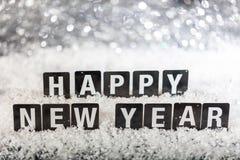 Szczęśliwy nowego roku tekst na śniegu, abstrakcjonistyczny bokeh zaświeca tło zdjęcia stock