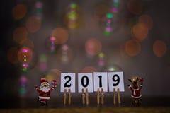 Szczęśliwy nowego roku 2019 tekst na papierach z clothespins z girlandy bokeh na tle Rok świnia zdjęcie royalty free