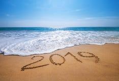 Szczęśliwy nowy rok 2019 jest nadchodzącego pojęcia oceanu piaskowatym tropikalnym plażą obraz royalty free