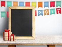 Szczęśliwy nowy rok na blackboard z prezentem i kolorowym chorągwianym sztandarem Zdjęcie Royalty Free