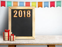 Szczęśliwy nowy rok 2018 na blackboard z prezentem i kolorowymi chorągwianymi półdupkami Obrazy Royalty Free