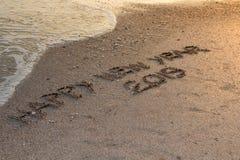 Szczęśliwy nowy rok pisać w piasku 2019, pisze na tropikalnej plaży z zdjęcia stock