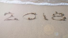 Szczęśliwy nowy rok 2018 2018 piszą na piaskowatej plaży z falowym pluśnięciem Zdjęcia Stock
