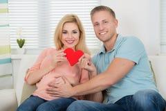 Szczęśliwy Oczekuje pary mienia serce W Domu Zdjęcie Stock