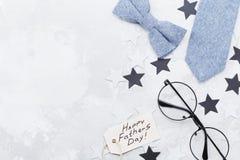 Szczęśliwy ojca dnia tło z powitania etykietki, szkieł, krawata, bowtie i gwiazdy confetti na stołowym odgórnym widoku, Mieszkani Zdjęcia Stock
