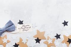 Szczęśliwy ojca dnia tło z powitanie etykietką, bowtie i gwiazda confetti na stołowym odgórnym widoku, Mieszkanie nieatutowy skła zdjęcia stock