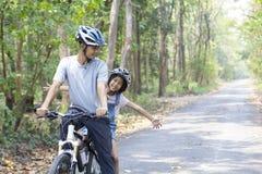 Szczęśliwy ojca i córki kolarstwo w parku zdjęcia stock