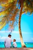 Szczęśliwy ojca i syna obsiadanie blisko morza podczas wakacje Zdjęcia Royalty Free