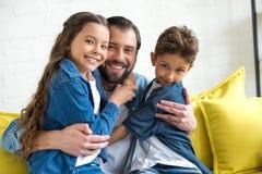 szczęśliwy ojciec ściska uroczych małe dzieci zdjęcia royalty free
