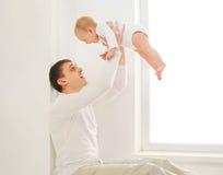 Szczęśliwy ojciec bawić się z dziecko domem w białym pokoju blisko okno Fotografia Stock