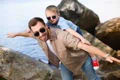 szczęśliwy ojciec daje piggyback syn blisko jeziora zdjęcia stock