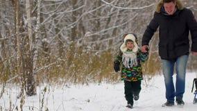 Szczęśliwy ojciec i bardzo śliczna szczęśliwa chłopiec, jego syn biegamy w śnieżnym zima parku chłopak się uśmiecha Atrakcyjna ro zdjęcie wideo
