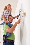 Szczęśliwy ojciec i mała dziewczynka maluje pokój zdjęcie royalty free