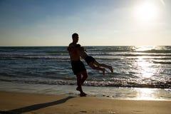 Szczęśliwy ojciec i syn bawić się na plaży przy zmierzchem na morzu obrazy royalty free