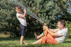 Szczęśliwy ojciec i syn bawić się w ogródzie przy dnia czasem obrazy stock