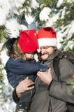 Szczęśliwy ojciec i syn jest ubranym Święty Mikołaj kapelusz Zdjęcie Stock