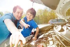 Szczęśliwy ojciec i syn pracuje na mechanizmu samochód Obrazy Stock