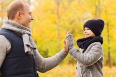 Szczęśliwy ojciec i syn robi wysokości pięć w parku Zdjęcia Royalty Free