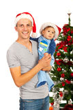 Szczęśliwy ojciec i syn z Santa kapeluszami Zdjęcia Stock