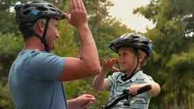 Szczęśliwy ojciec na rowerze z jego synem zbiory