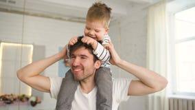 Szczęśliwy ojciec niesie jego uśmiechniętego syna na szyi i patrzeje each inny w sypialni zbiory