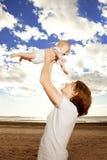 Szczęśliwy ojciec rzuca up chłopiec przeciw niebieskiemu niebu Zdjęcie Royalty Free