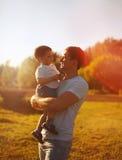 Szczęśliwy ojciec trzyma dalej wręcza dziecko synowi ciepłego jesień wieczór, pogodna rodzinna fotografia zdjęcia stock