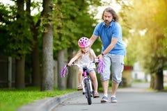 Szczęśliwy ojciec uczy jego małej córki jechać bicykl Dziecko uczenie jechać rower obrazy royalty free