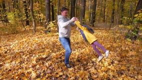 Szczęśliwy ojciec wiruje jego małego szczęśliwego dziecka w jego rękach przy parkiem zbiory