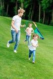 szczęśliwy ojciec z córką i synem bawić się z kanią podczas gdy biegający na zielonej łące fotografia royalty free